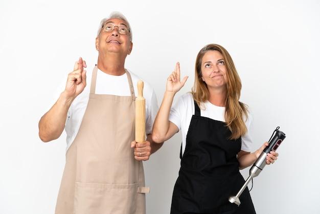 Pareja de chefs de mediana edad aislado sobre fondo blanco con los dedos cruzando y deseando lo mejor