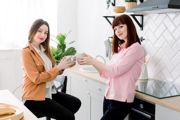 Pareja de chicas lesbianas disfruta de un café en casa tomando algo. dos jóvenes hermosas mujeres adultas beben té en cocina moderna interior blanco