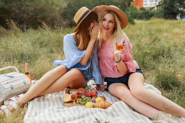 Pareja de chicas maravillosas que pasan las vacaciones en el campo, bebiendo vino espumoso.