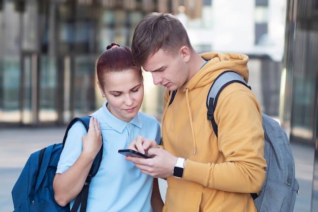 Pareja, chico serio y chica mirando atentamente el teléfono celular, el chico está sirviendo, navegando en su teléfono inteligente