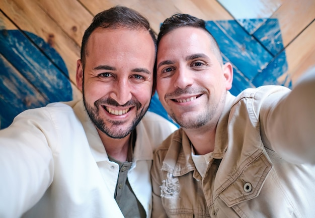 Pareja de chicos gays sonrientes tomando un selfie mirando a la cámara