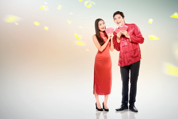 Pareja china asiática en vestido cheongsam con sobres rojos