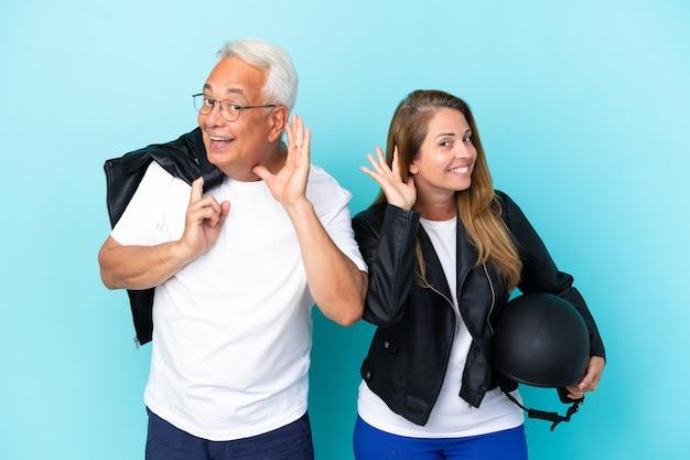 Pareja de ciclistas de mediana edad con un casco de motocicleta aislado sobre fondo azul escuchando algo poniendo la mano en la oreja