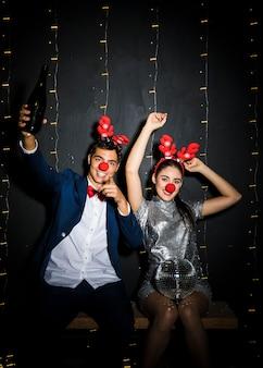 Pareja con cintas de astas de ciervo y narices divertidas con bola de discoteca y botella