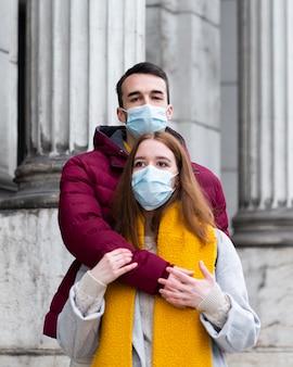 Pareja en la ciudad con máscaras médicas