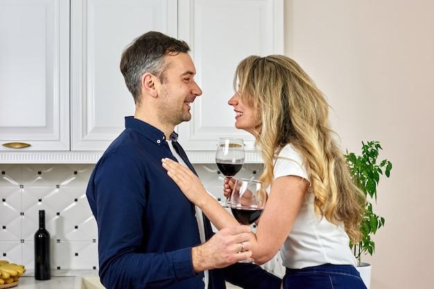 Una pareja en la cocina bebiendo vino tinto