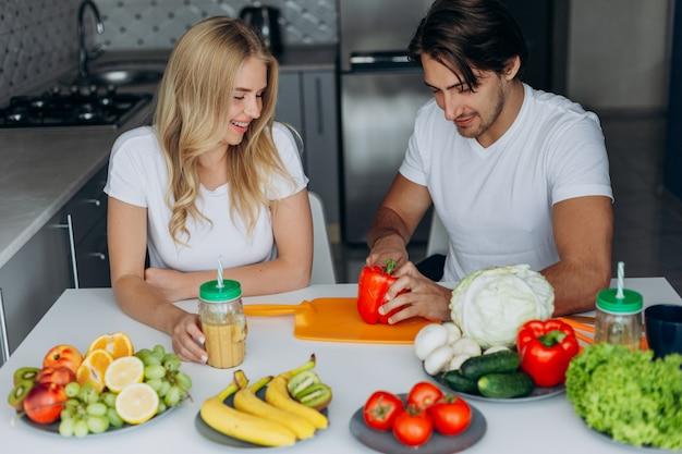 Pareja en la cocina sentado en la mesa con comida sana.