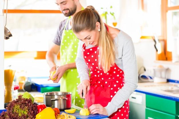 Pareja cocinando en la cocina doméstica comida sana