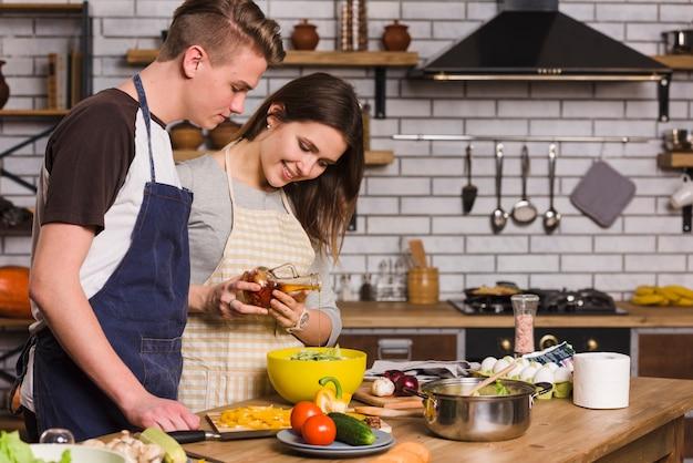 Pareja cocinando ensalada vegetariana con verduras frescas