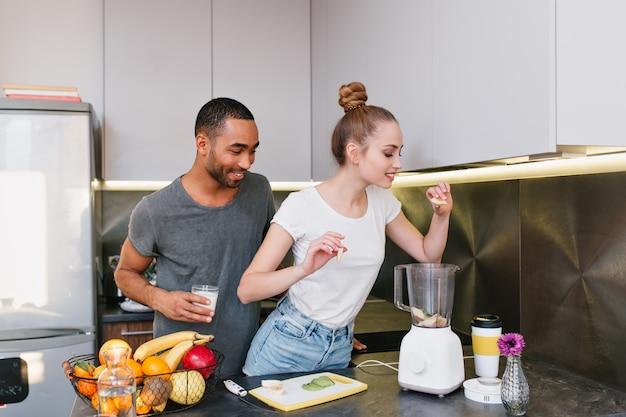 Pareja cocinando juntos en la acogedora cocina. chica pone frutas en una licuadora, rubia adora una dieta saludable. par pasar tiempo en la casa moderna.
