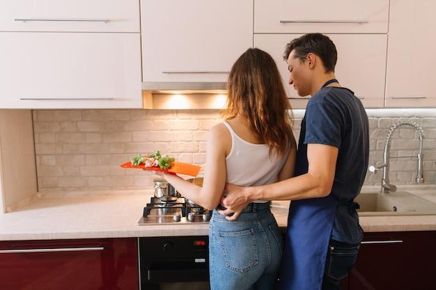 Pareja cocinando juntos en la cocina en casa