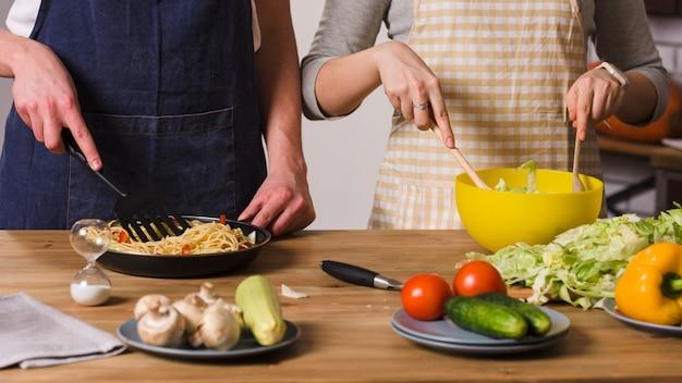Pareja cocinando en la mesa en la cocina