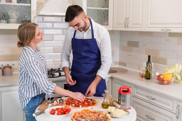 Pareja cocinando pizza con champiñones y verduras