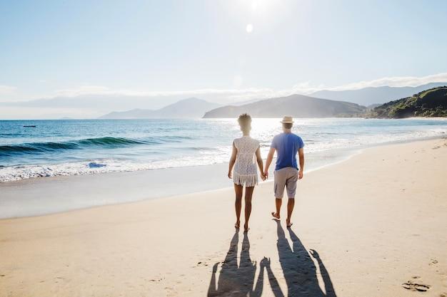 Pareja cogiéndose las manos y andando en la playa