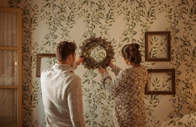 Pareja colgando guirnalda de navidad en la pared