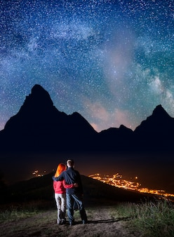 Pareja en la colina bajo las estrellas brillantes