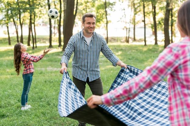 Pareja colocando una manta en el césped cerca de su hija jugando un balón de fútbol en el jardín