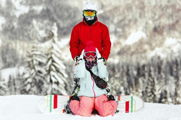 Pareja en coloridos trajes de esquí plantea en la colina en algún lugar de las montañas
