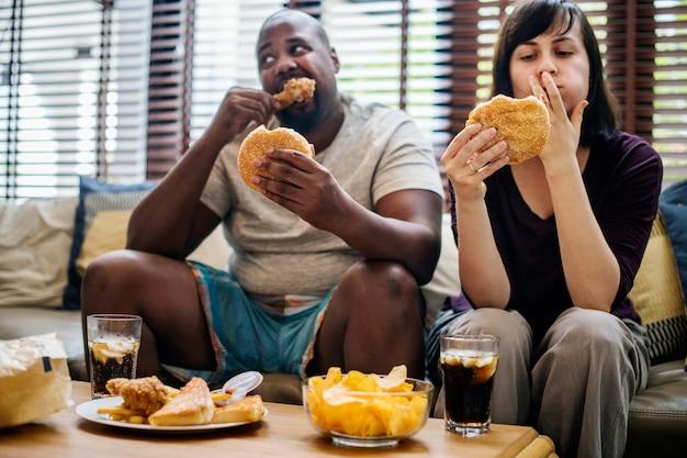 Pareja de comida rápida en el sofá