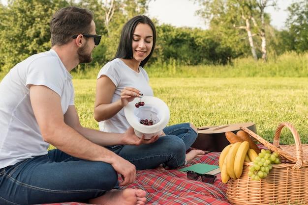 Pareja comiendo cerezas sobre manta de picnic