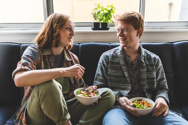 Pareja comiendo ensalada healty en casa en el sofá