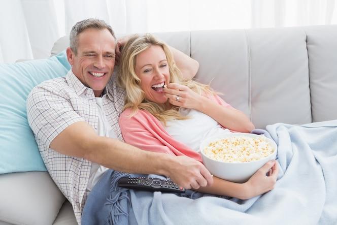 Pareja comiendo palomitas de maíz mientras ve la televisión