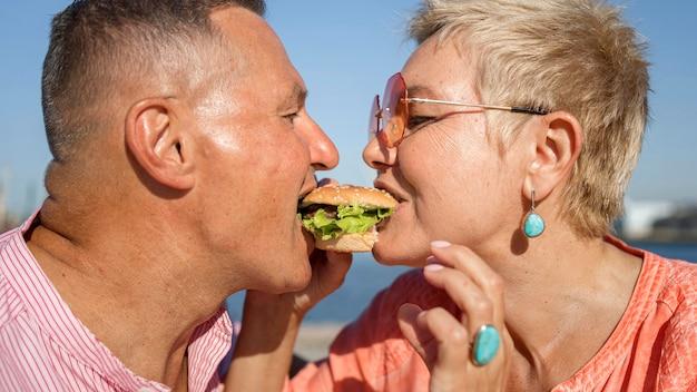 Pareja compartiendo una hamburguesa al aire libre
