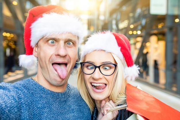 Pareja de compras en tiempo de navidad tomando un selfie divertido