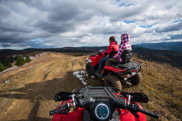 Pareja conduciendo un atv en frente en la cima de la montaña bajo el cielo con nubes en las montañas