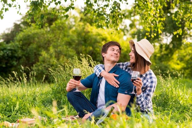Pareja con copas de vino abrazando en la naturaleza