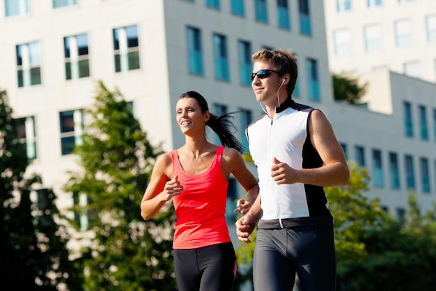 Pareja corriendo como deporte en la ciudad