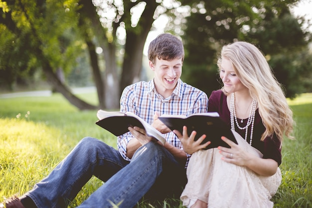 Pareja de cristianos blancos disfrutando de la lectura de la biblia en medio de un campo