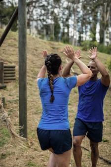 Pareja dando cinco el uno al otro durante la carrera de obstáculos