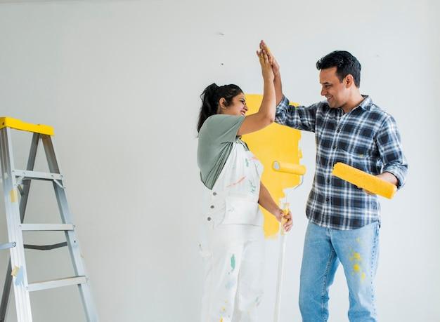 Pareja dando un máximo de cinco mientras renovando su nueva casa