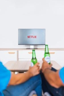 Pareja de cultivos con cerveza viendo series de televisión