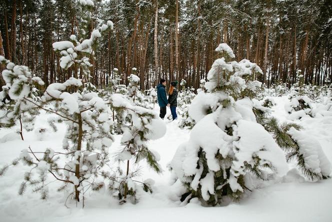 Pareja de enamorados caminando en el bosque de pinos cubiertos de nieve. historia de amor de invierno.
