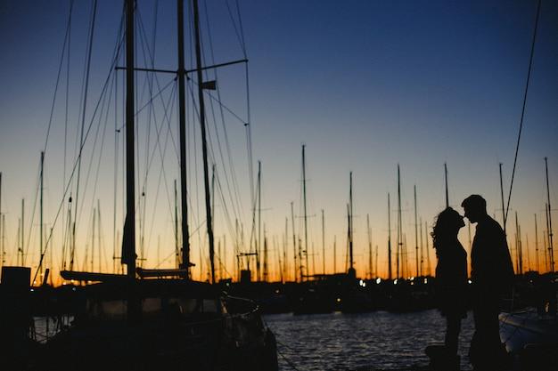 Pareja de enamorados celebrando abrazándose, amor en un puerto con barcos
