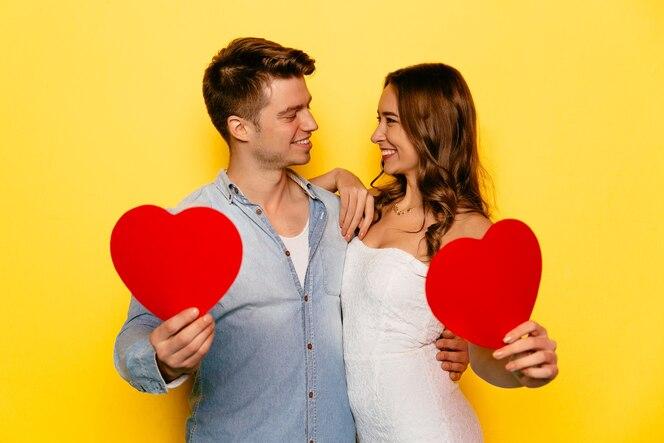 Pareja de enamorados celebrando el día de san valentín, sosteniendo corazones rojos, mirando el uno al otro.