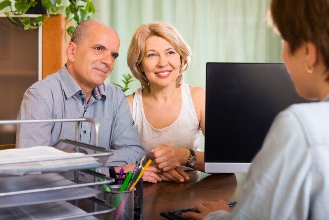Pareja de jubilados hablando con un empleado