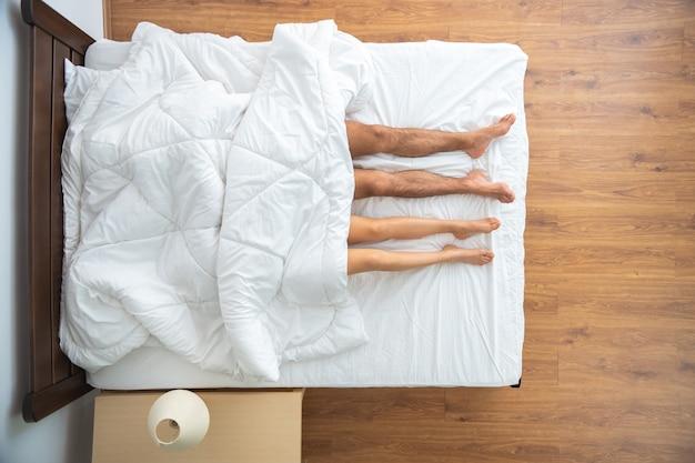 La pareja debajo del edredón acostado en la cama. vista desde arriba