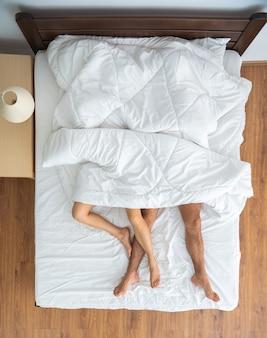 La pareja debajo de la manta tendida en la cama. vista desde arriba
