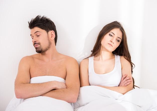 Pareja debajo de las mantas en la cama se alejaron el uno del otro.