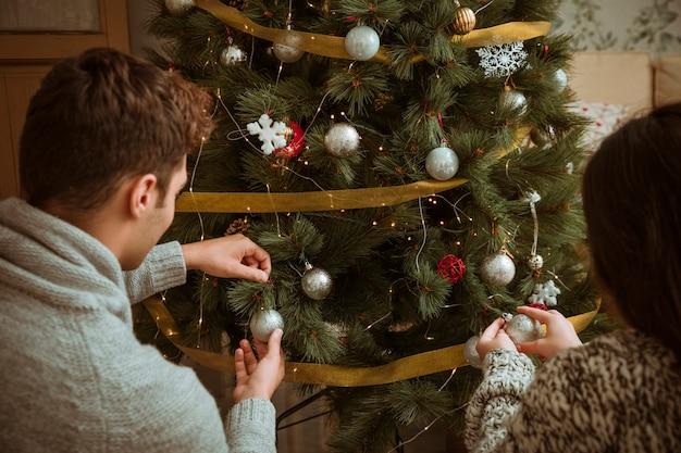 Pareja decorando arbol de navidad con bolas de plata.