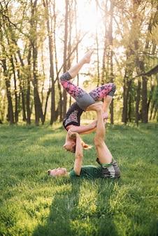 Pareja deportista practicando acro yoga en pasto verde