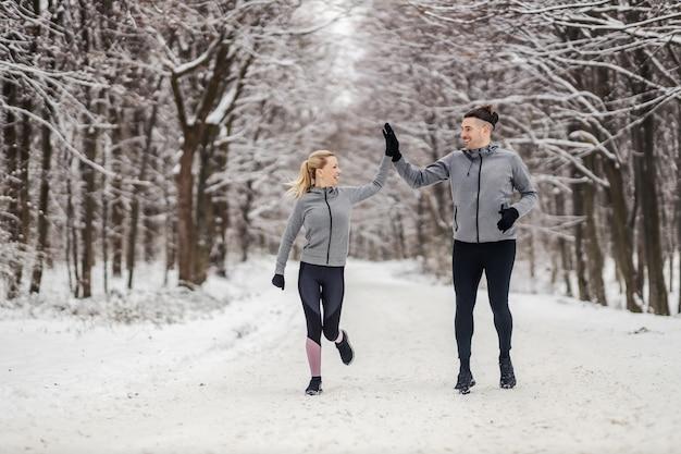 Pareja deportiva corriendo juntos en un día nevado de invierno en el bosque. se dan cinco el uno al otro. fitness al aire libre, fitness de invierno, hábitos saludables.