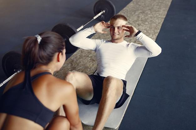 Pareja deportiva en un entrenamiento de ropa deportiva en un gimnasio
