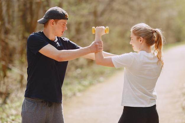 Pareja deportiva entrenando en un bosque de verano