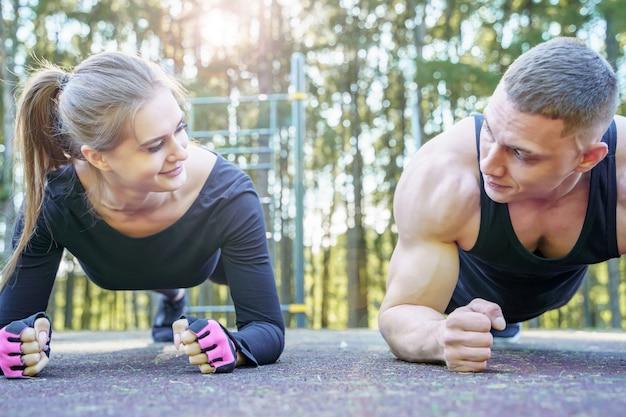 Pareja deportiva haciendo ejercicio tabla al aire libre