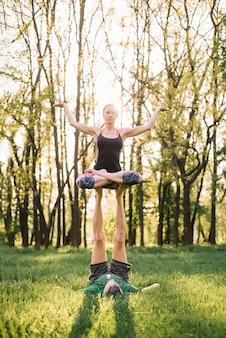 Pareja deportiva haciendo ejercicios de acroyoga en tierra verde vidriosa