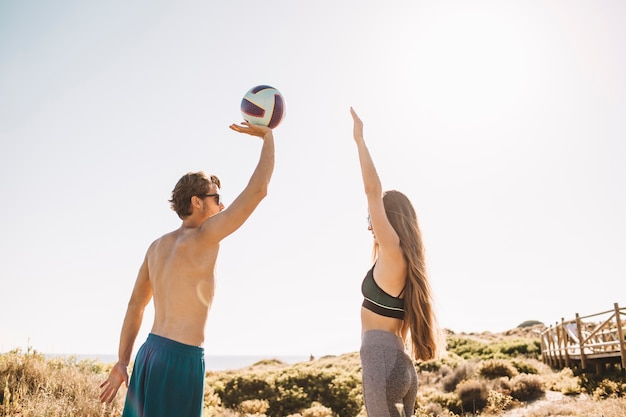 Pareja deportiva jugando al voleibol en la playa